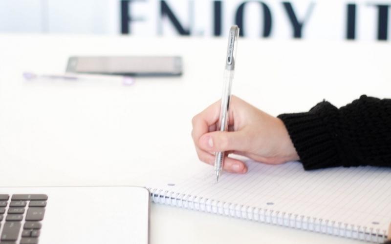 persona scrive su foglio di carta